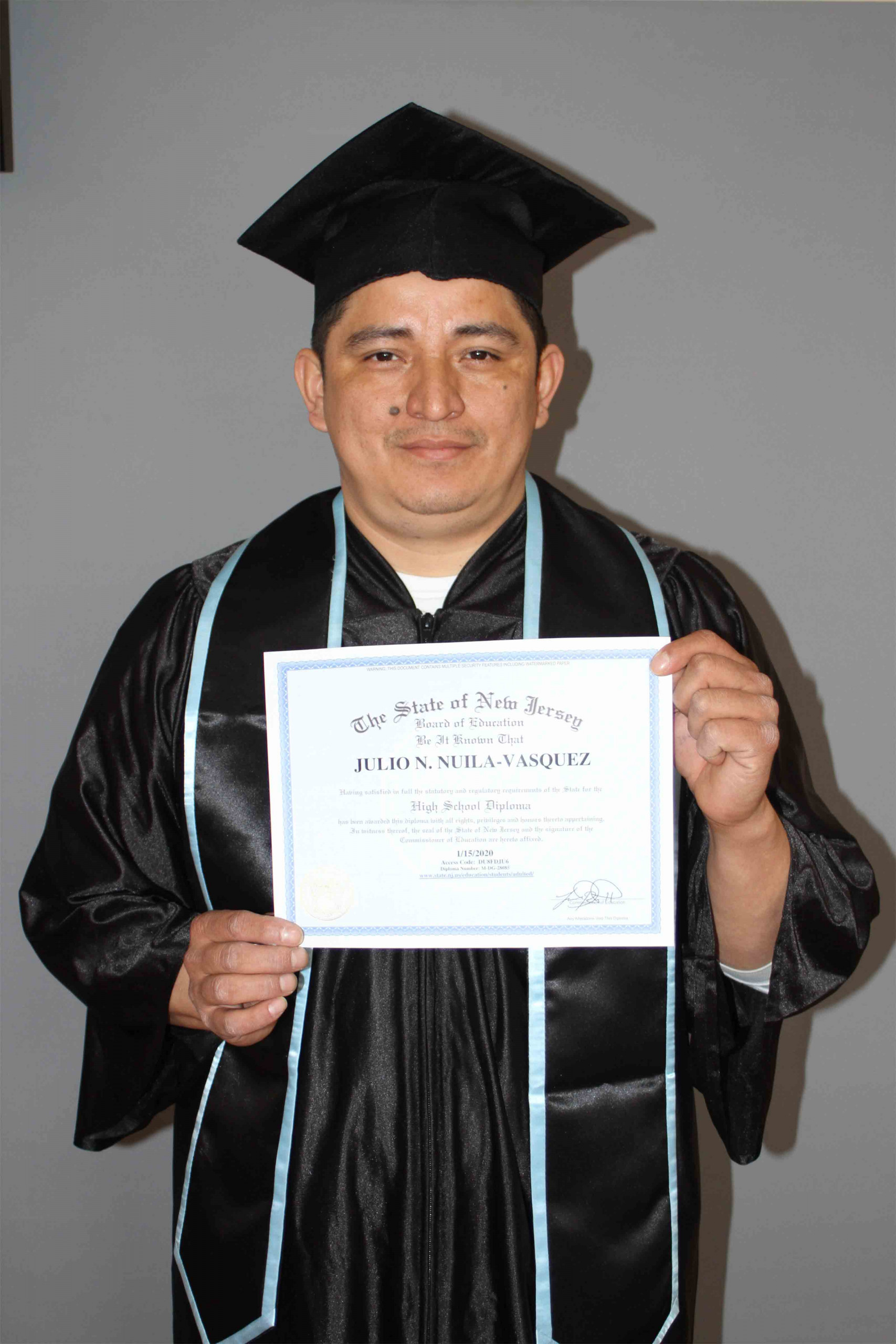 man dark hair holding a high school diploma