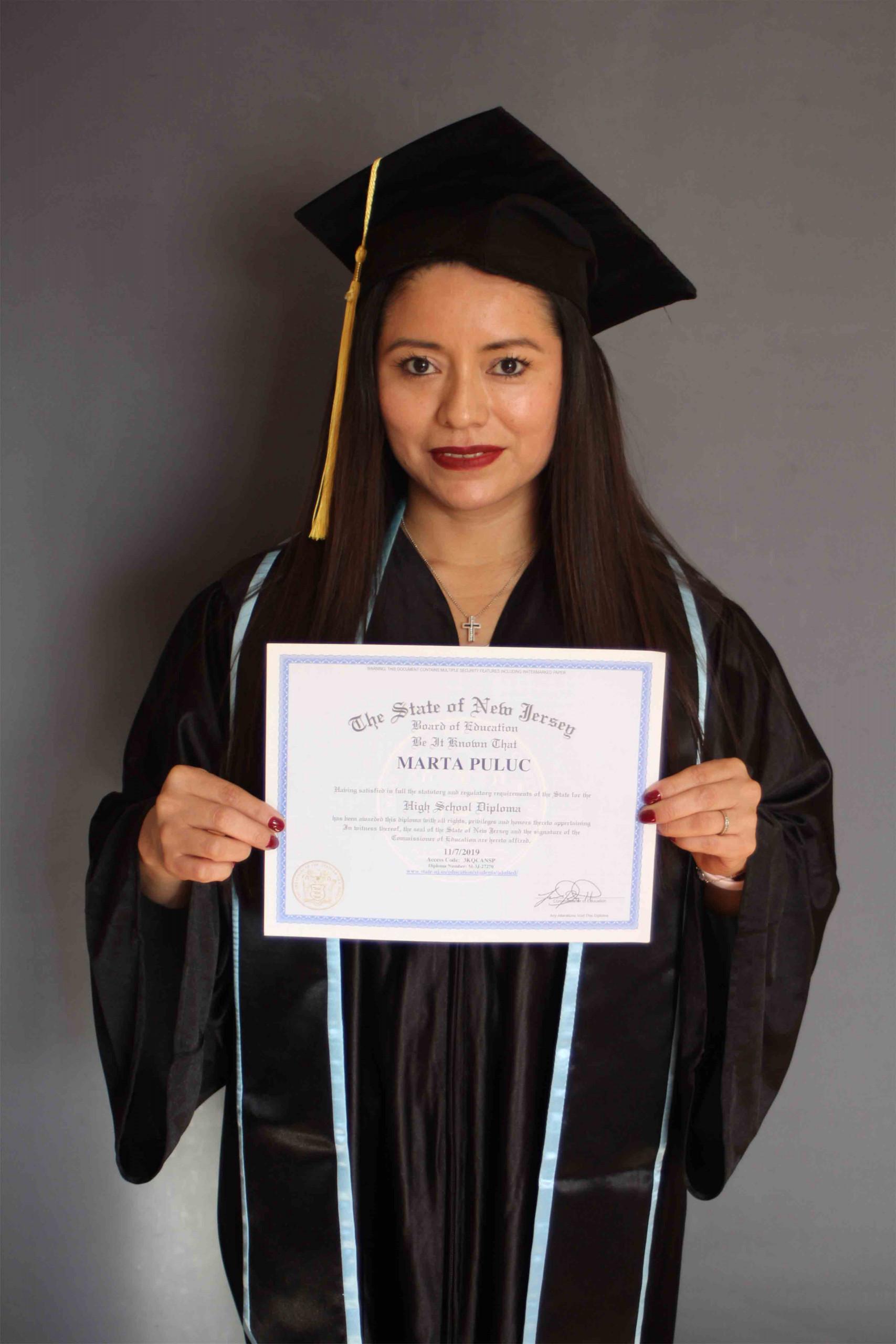 woman dark hair holding a high school diploma